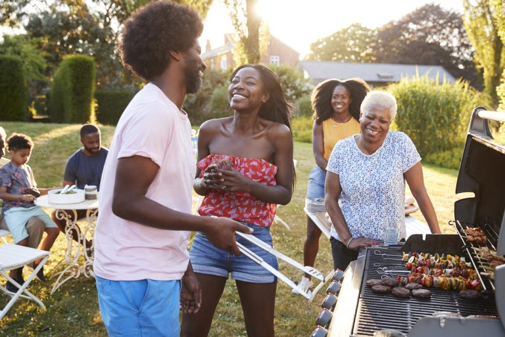 A group of people smile and laugh as a young man and a grandmother work the grill.