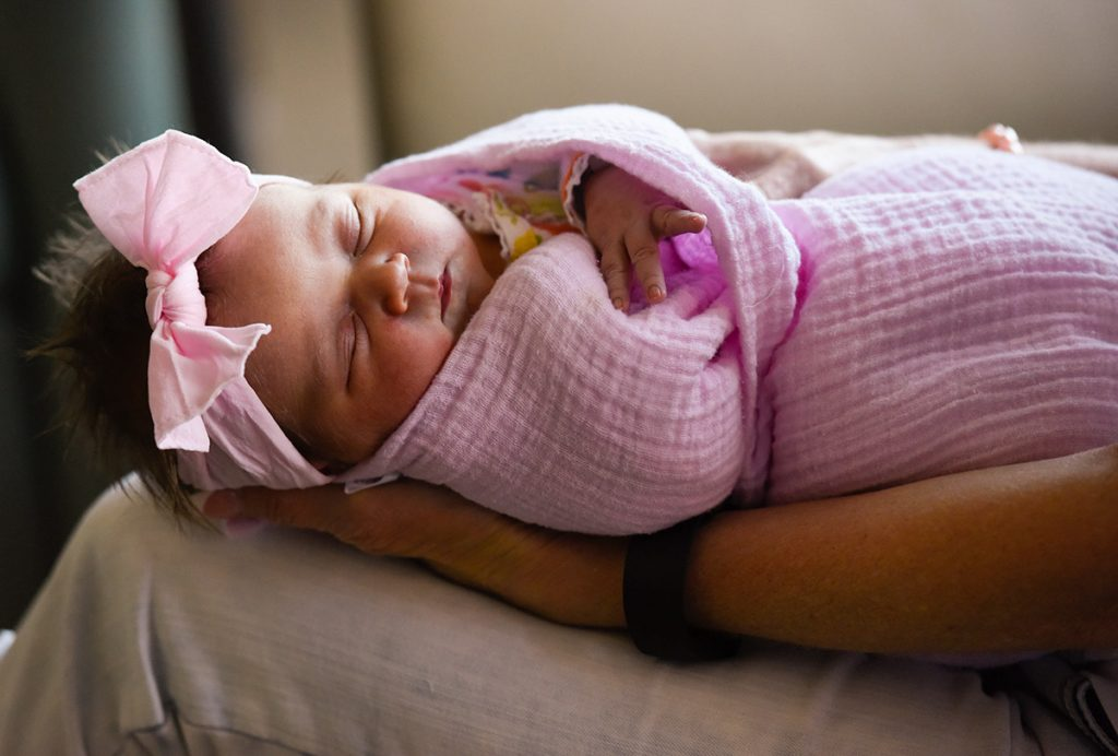 a newborn baby snoozes wearing a pink bow. Wrapped in a pink blanket, Eloise Burford was the first baby born in Highlands Ranch, CO