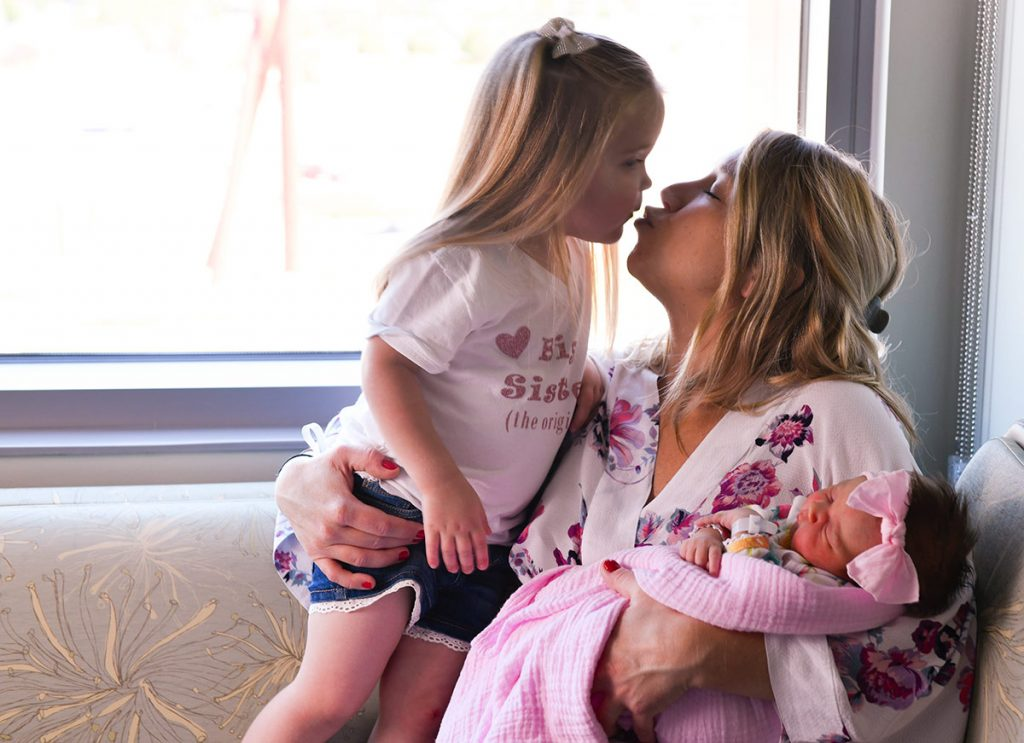 Hadley Burford gets a kiss from her mom as Elésha Burford holds Eloise, the first baby ever born in Highlands Ranch, CO.