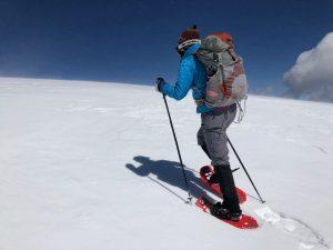 women snowshoeing up a mountain