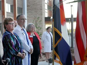 leaders stand looking at the flags