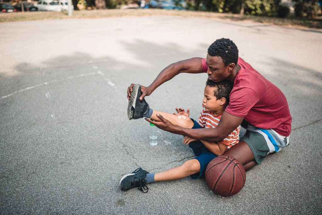A father checks his son's ankle while sitting on the ground playing basketball outside.