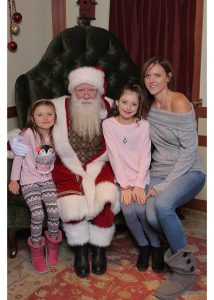 Sarah Hugo is photographed with two girls and Santa Claus