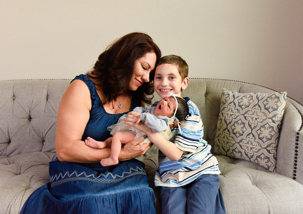 A young boy and his grandmother hold a 3-day-old baby in Greeley.