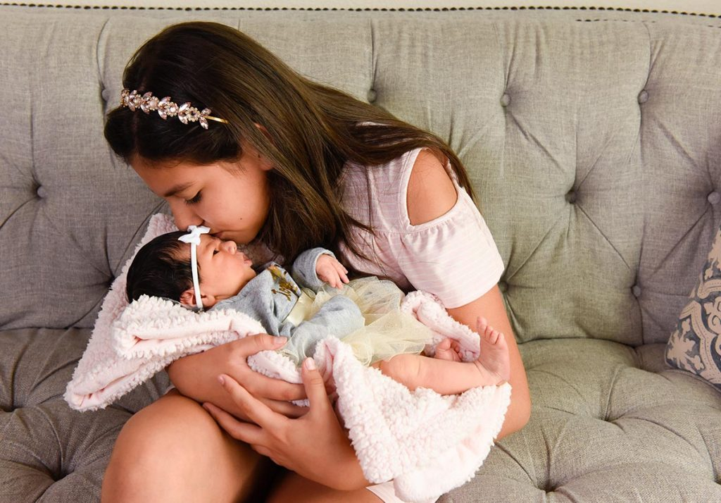 A 10-year-old kisses her  new baby sister.
