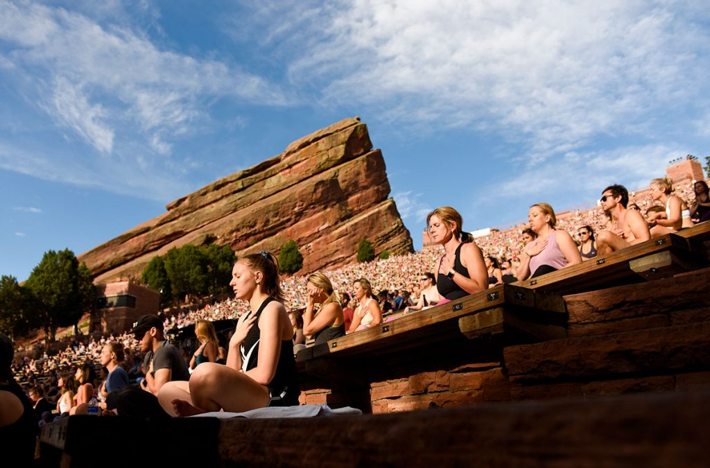 People sit during a yoga class at Red Rocks Amphitheater.