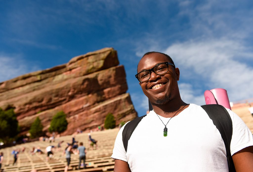 An African American man with his yoga mat slung over his shoulder at Red Rocks Amphitheater.