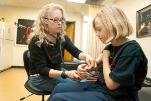 brandi, a two-time living donor, examines a student's armn