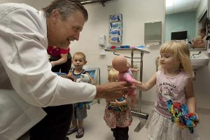 ER doctor hands doll to little girl in emergency room