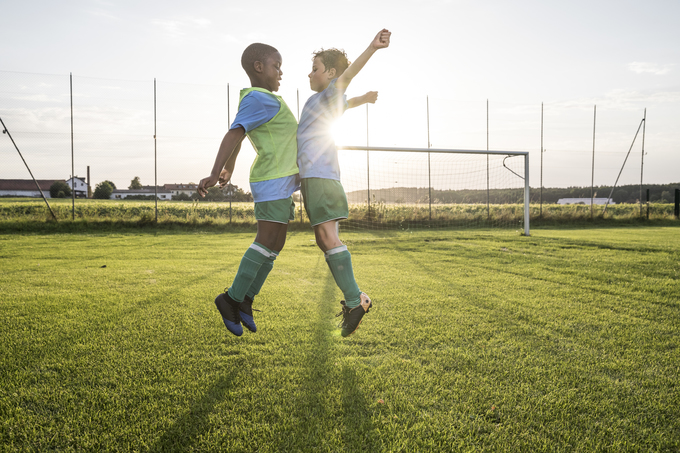 Young children celebrate on the soccer field with a chest bump in this photo.