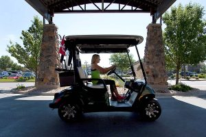women in golf cart outside medical fitness building