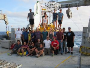 about 20 crew members stand on a massive ship in the middle of the ocean for a photo