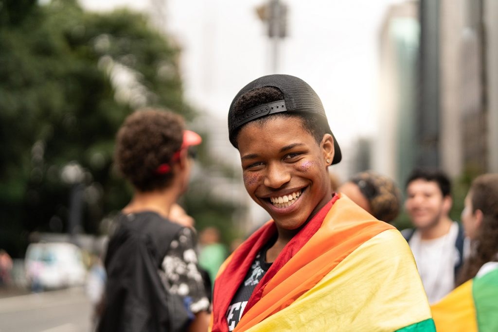 a teen boy with a Pride flag wrapped around his shoulders
