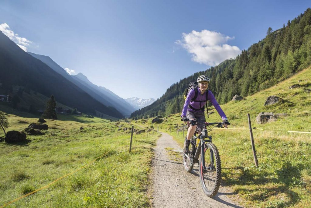 a woman rides a bike on a mountain path, one way of to take time for yourself.