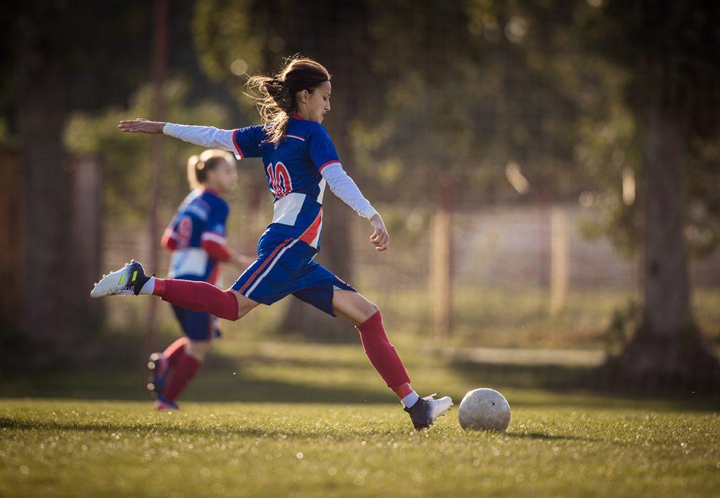 A teenage girl kicks a soccer ball during a game.
