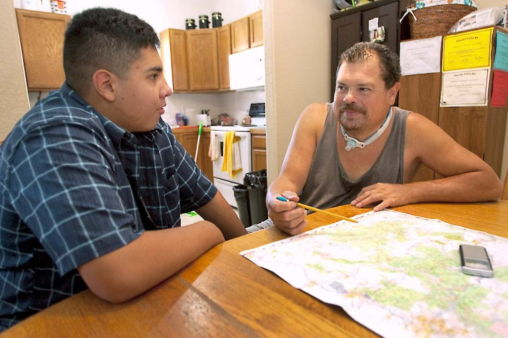 father, who UCHealth helped in avoiding risky surgery, sits with his son at a table, now able to travel because he feels so much better.