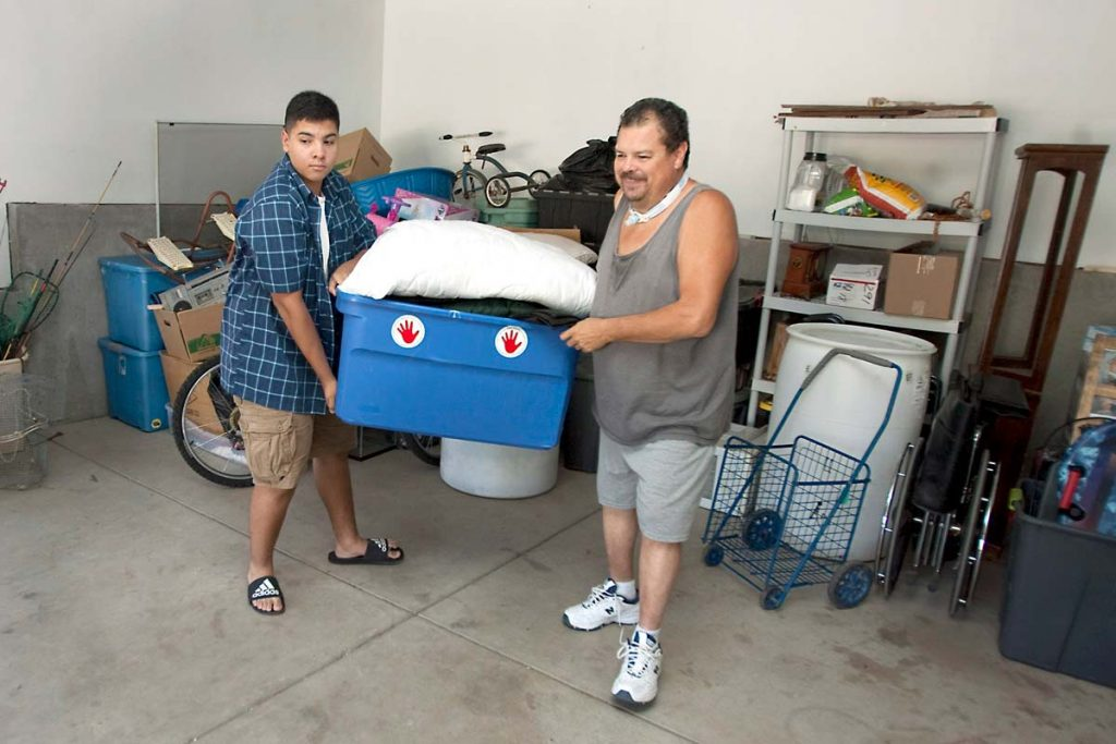 father and son work together to move camping gear into a truck, getting ready for a trip that was possible because John avoided risky surgery.