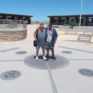 father and son standing on the four corners markers