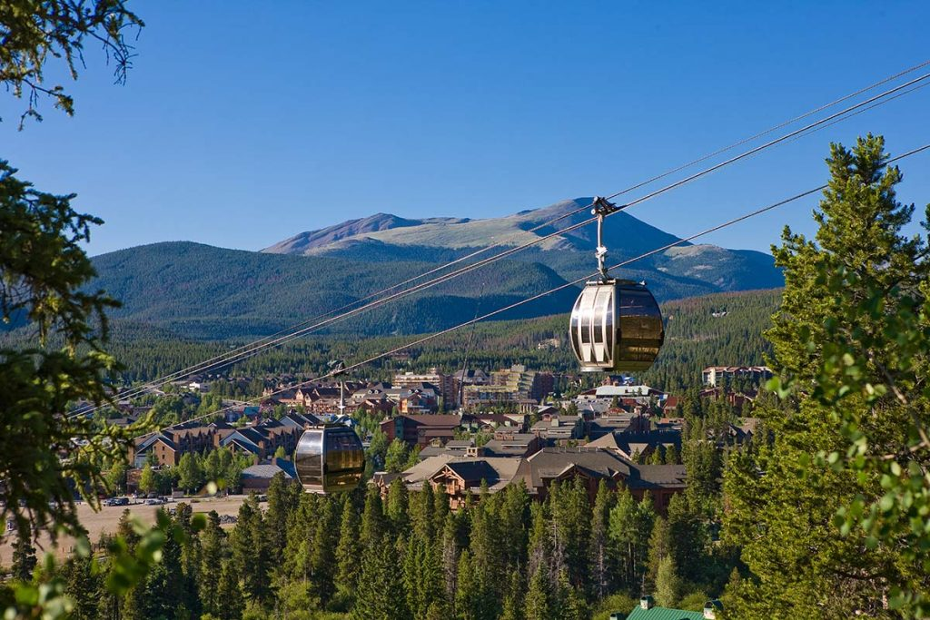 One of the free gondolas in Colorado is the BreckConnect gondoal in Breckenridge. Here you see a gondola car above the slopes with a mountain in the background.
