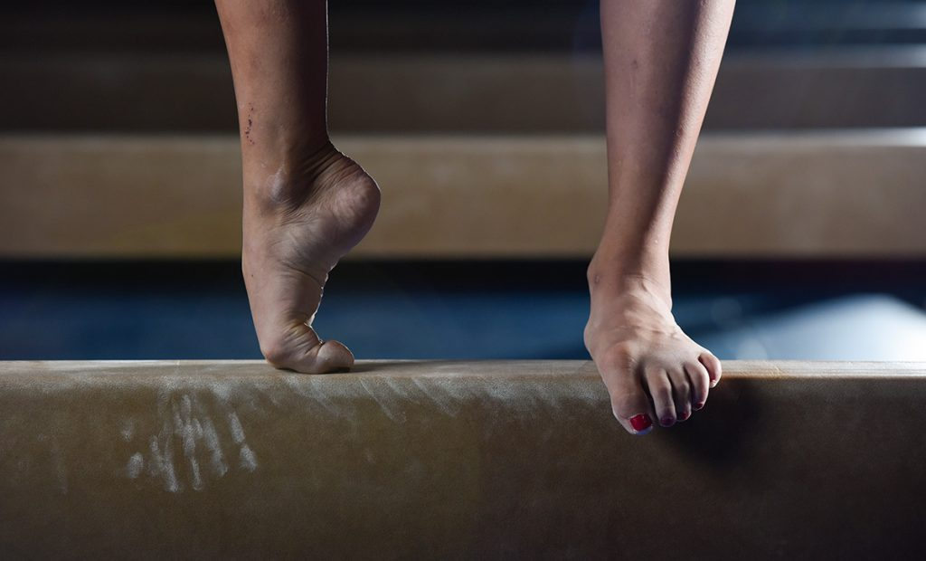 Jessica López closeup of her feet on a balance beam.