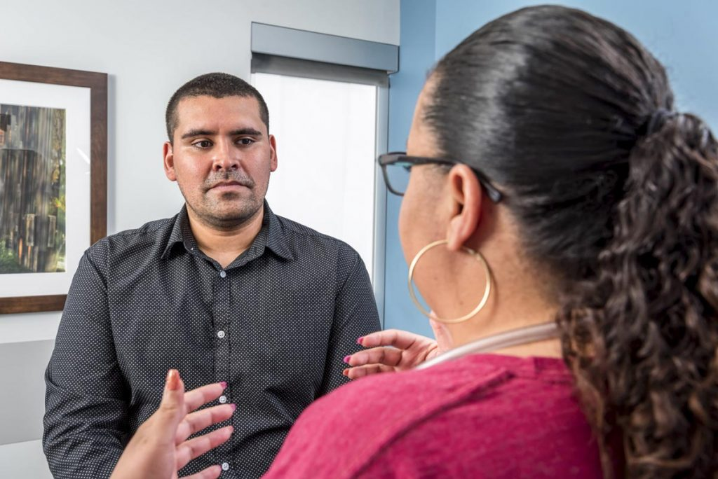 A care provider talks with a gentleman at a doctor's office. UCHealth is dedicating more than $100 million to enhance behavioral health care in Colorado. Clinical social workers will work alongside primary care physicians to help patients with behavioral health care needs.