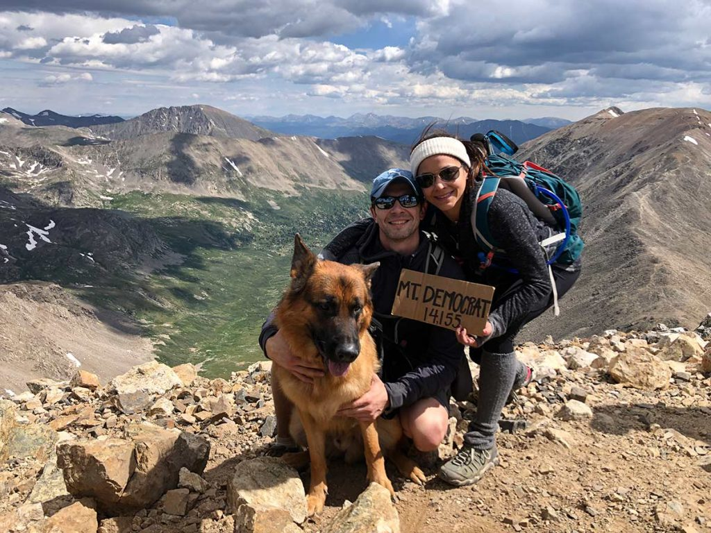 Olympic gymnast Jessica López at the top of a 14er with her boyfriend and her dog.