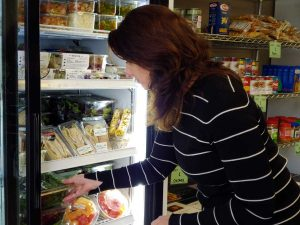 Women stocks cooler at a food pantry in Fort Collins.