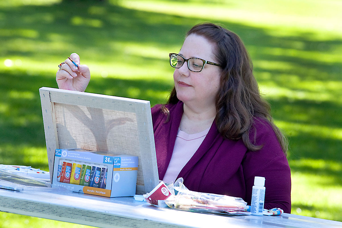Karla enjoys painting in the park because she's managed her diabetes with diabetes education.