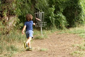 4-year-old puts his disc into the basket at one of the great disc golf courses in Colorado.