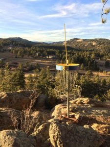 disc golf basket sits on top of a rock ledge with mountains in the background.