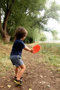 4-year-old boy gets ready to toss a disc at a basket while his father watches one of the great disc golf courses in Colorado.