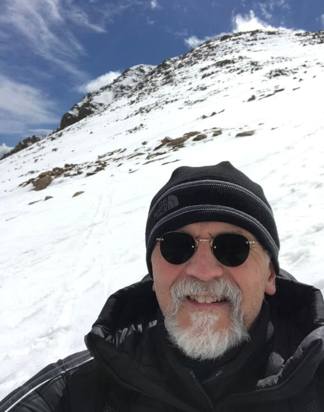 Dr. Corky Dillon on Mt. Bierstadt after surgery for a rare lung illness. This shows a headshot with snow on the peak behind him.