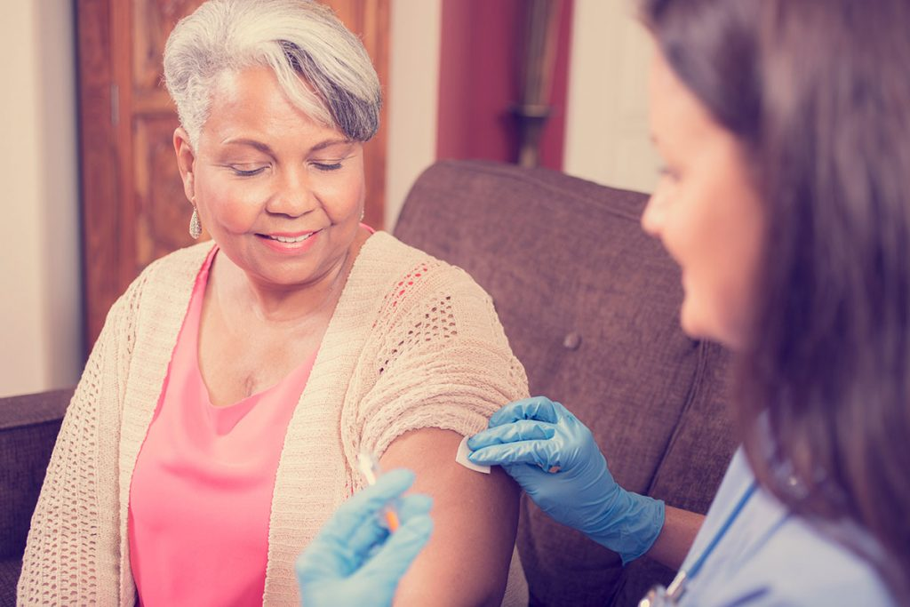 A woman gets a flu shot from a provider