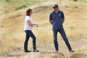 kim holds clipboard while talking with Torin in a field.