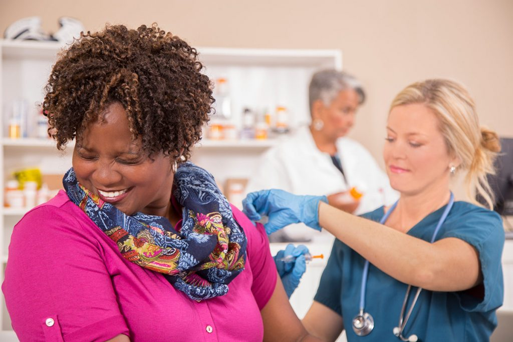 A nurse gives a woman a flu shot as she turns away and cringes