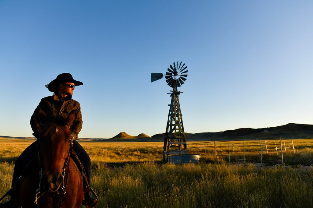 Nathan Kissack poses with an old fashioned windmill ner his family's ranch in Wyoming.