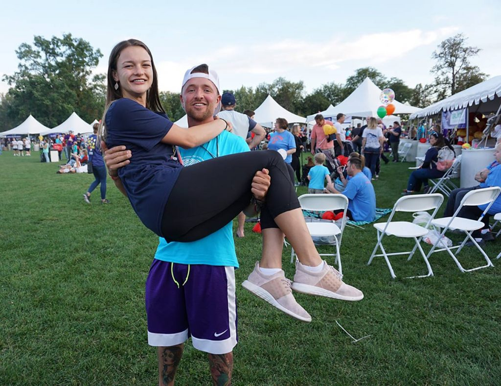 Rancher and cancer survivor Nathan Kissack holds one of his nurses, Danielle McAvoy, in his arms during the Light the Night celebration at Washington Park in September, 2019 in Denver.