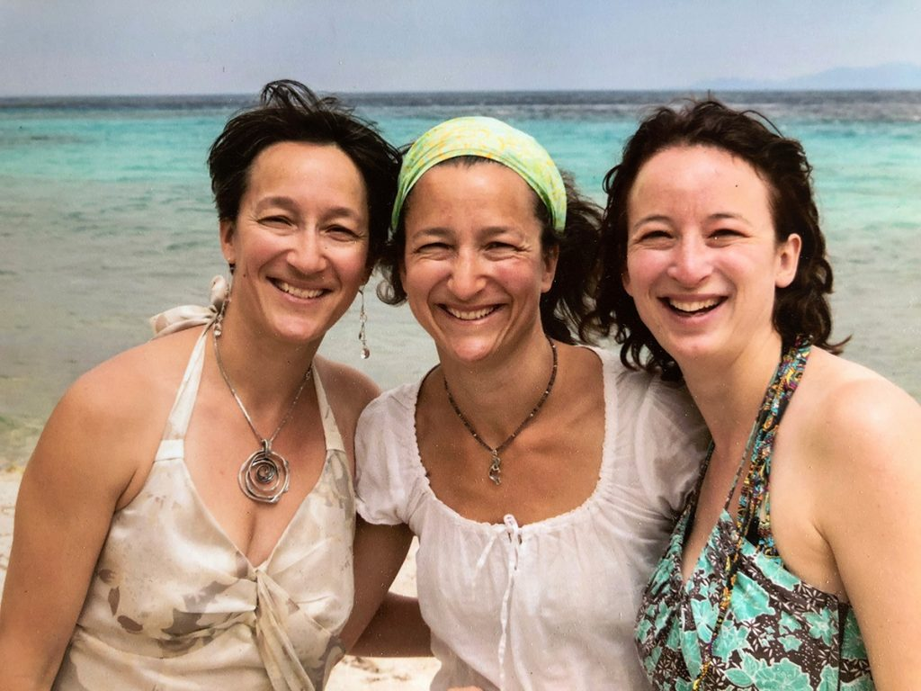 Sisters Alex Mathisen, Thea Pallut and Laura Gallagher pose for a photo on the beach in Greece in this photo.