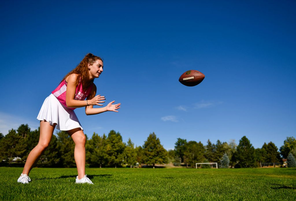 Ella Johnson anticipates catching a football, which has been thrown her way.