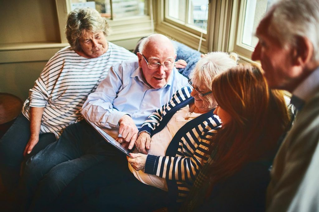 A family gathers around an elderly woman who is holding a tablet to illustrate palliative care telehealth.