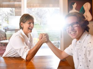 grandma and grandson arm wrestle at the kitchen table. Betty nas her strength back after having the first successful hepatitis C-infected liver transplant at UCH.