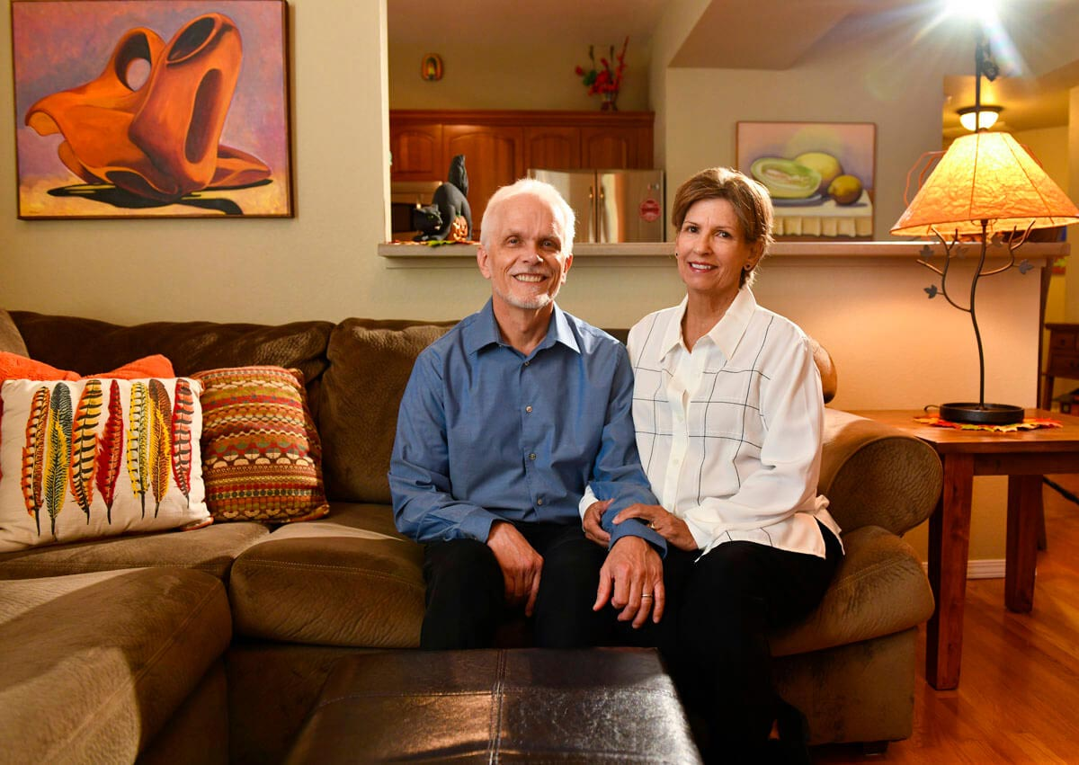 husband and wife sit together in their home.