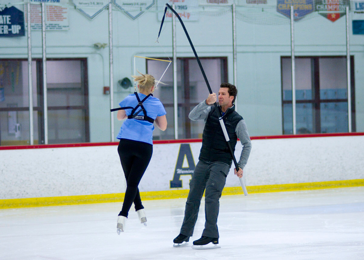 skater turning in air while coach holds a harness to support her landing.