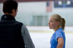 coach and skater talk at ice rink