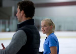 skater talking to coach at ice rink.