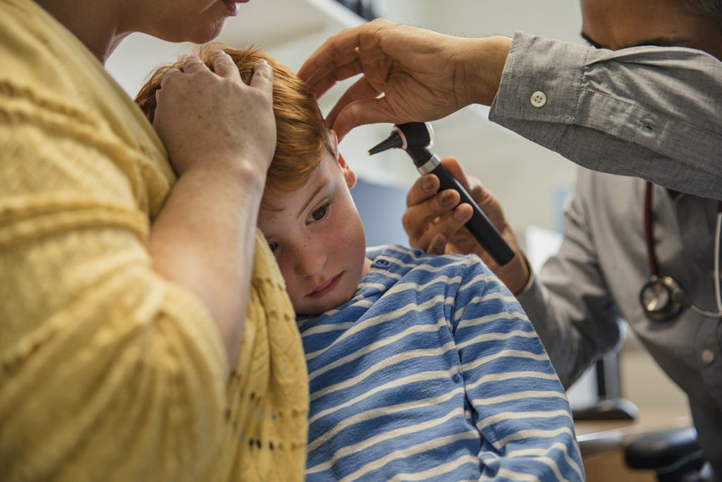 A young boy has his ear examined.
