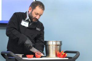 chef cuts a pomegranate in quarters.