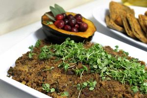 Quinoa stuffing with pea microgreens on top and a side roasted squash edible decor filled with cranberries and sage.