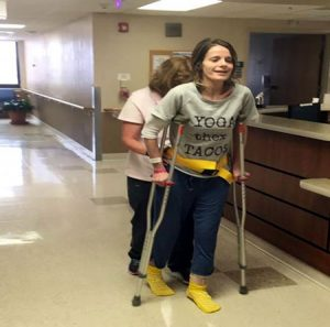 women walking with crutches and nurses help through a hospital hallway.