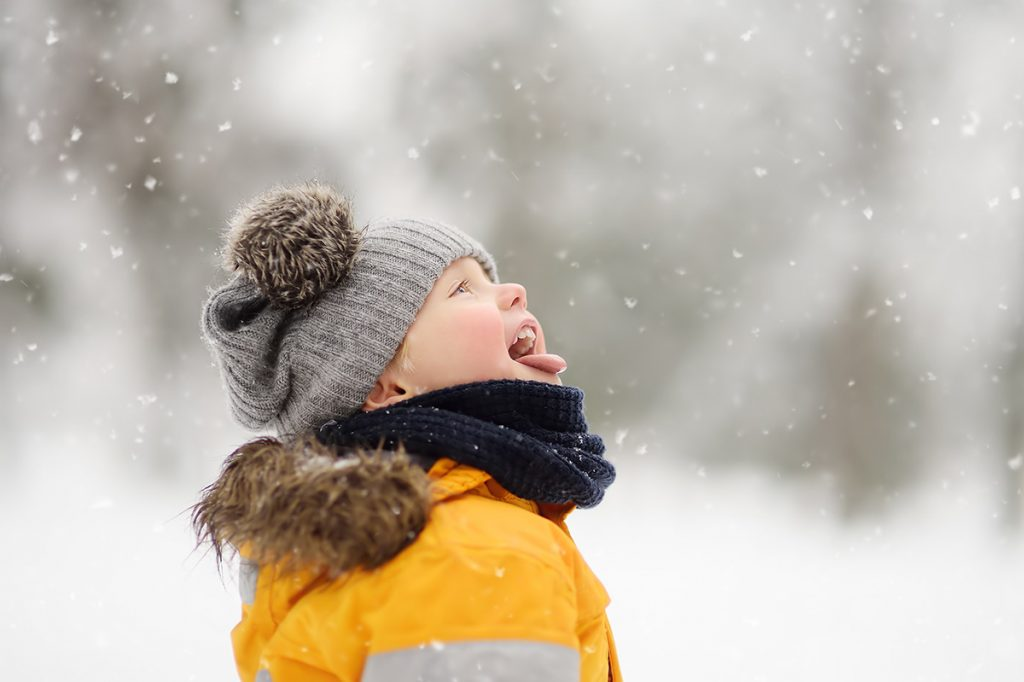 A kid sticks his tongue out to try and catch snowflakes. Colorado weather can cause frostbite.